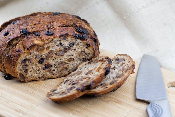 cutting fruit bread with knife on the cutting board