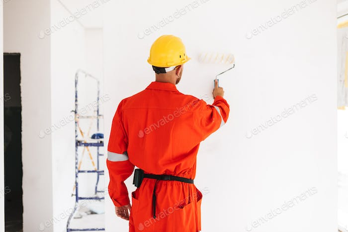 Young foreman standing from back in orange work clothes and yell