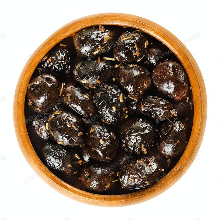 Französische schwarze Oliven mit Kräutern in Holzschale