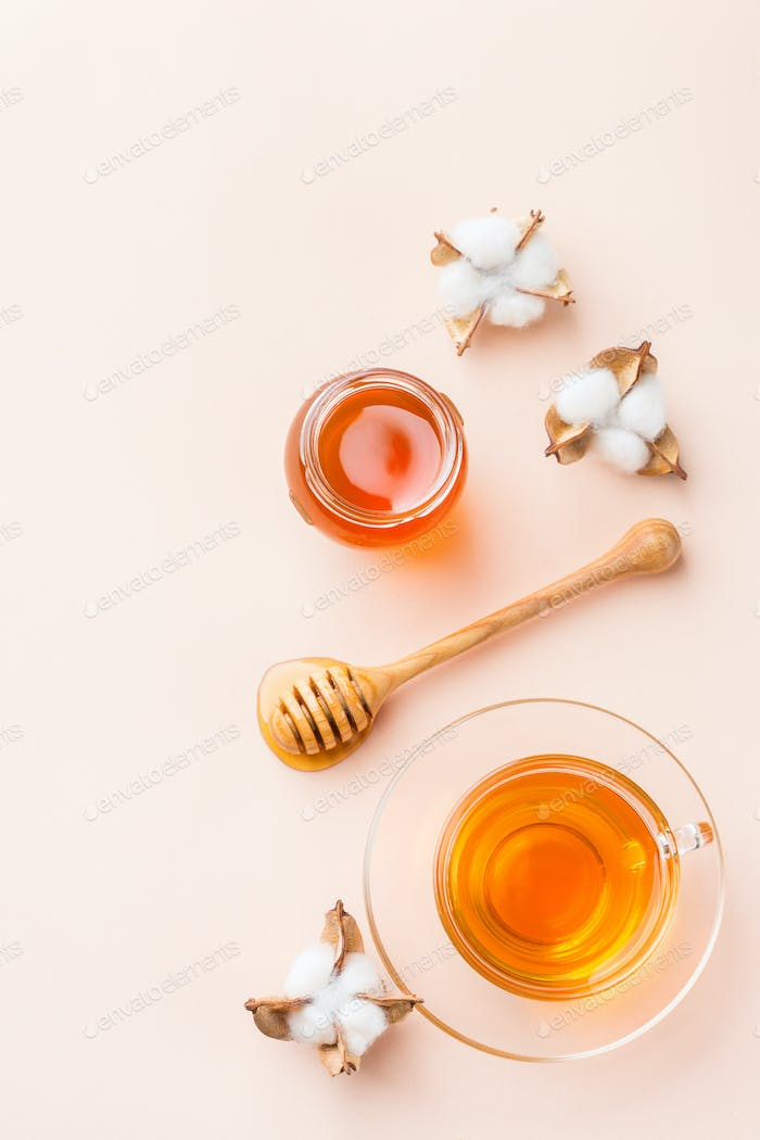 Cup of tea with honey on pastel pink, apricot background