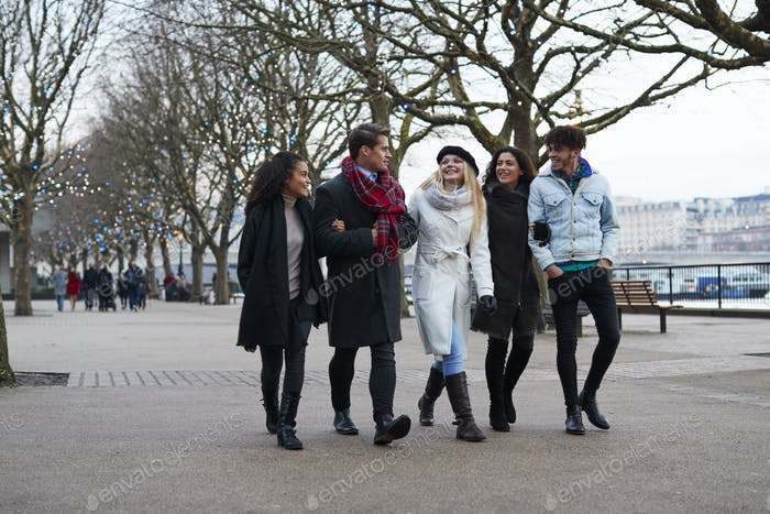 Friends Walking Along South Bank On Winter Visit To London