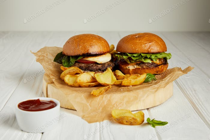 Junk food diner with hamburgers and french fries served with sauce on table