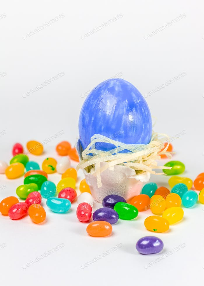 Blue easter egg in little nest decorated with jelly belly