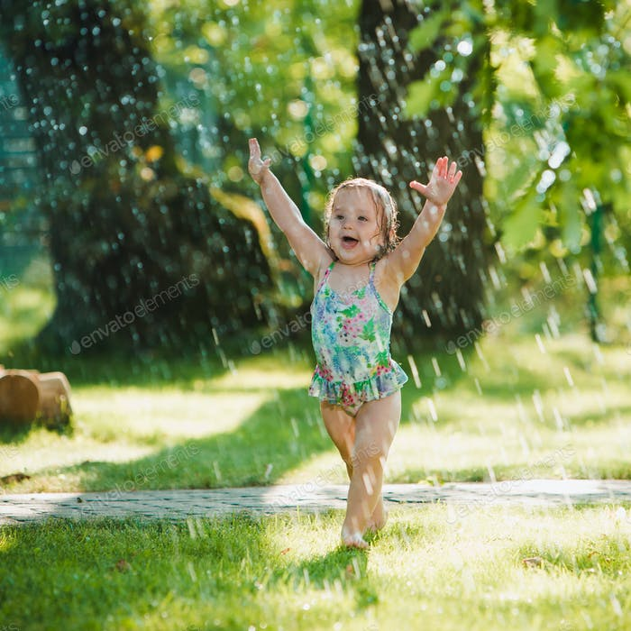 The little baby girl playing with garden sprinkler.
