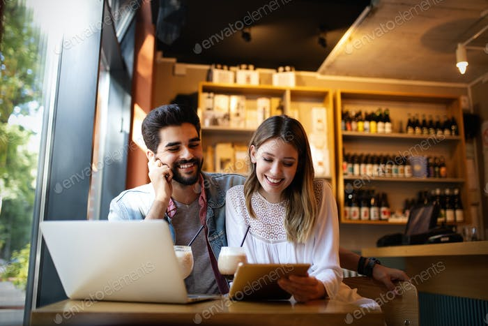 Young couple is working in cafe on laptop and smiling