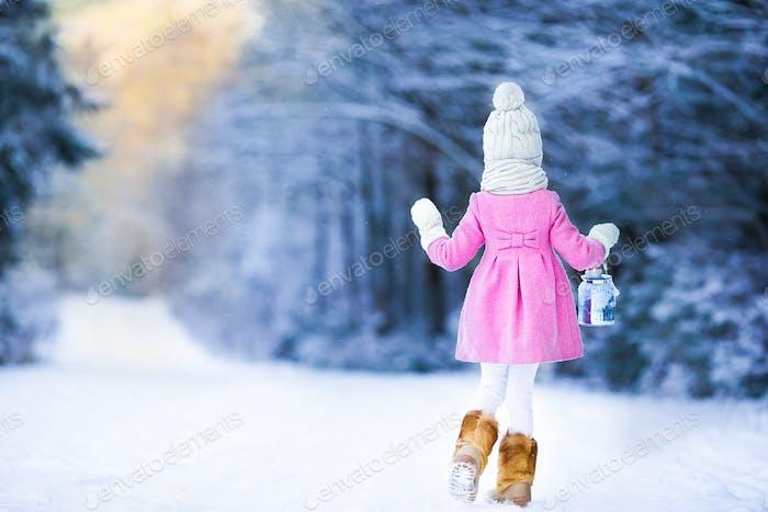 Entzückende Mädchen mit Taschenlampe und Kerze im Winter auf Weihnachten Abend im Freien