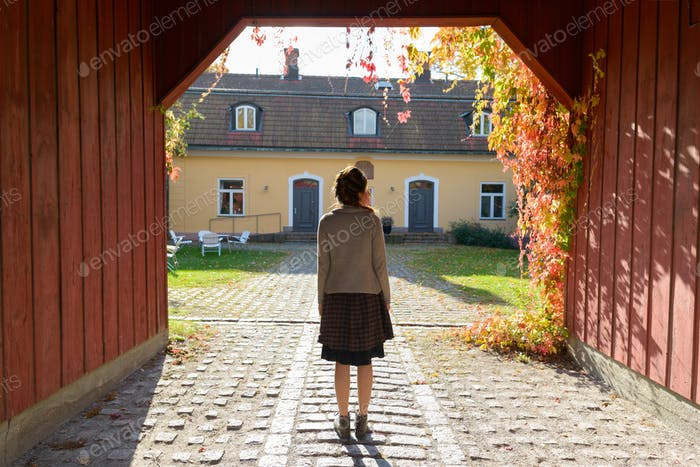 Back view of young woman standing in wooden entrance of elegant suburban house