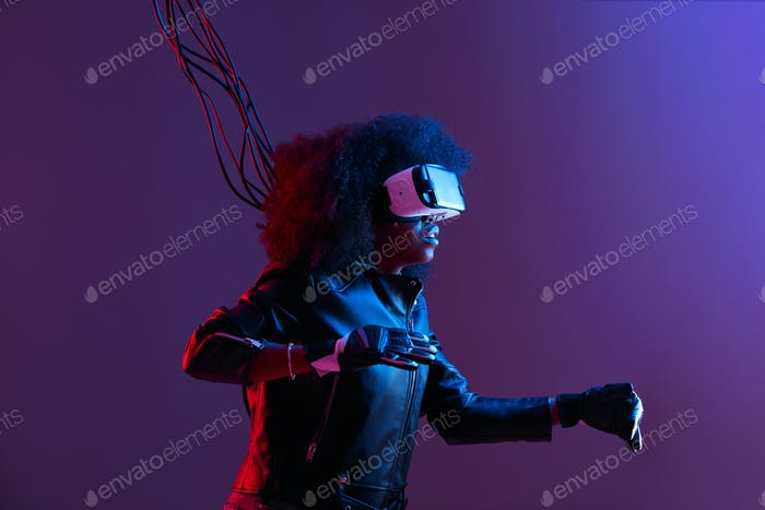 Thumbnail for Mod curly dark haired girl dressed in black leather jacket and gloves uses the virtual reality