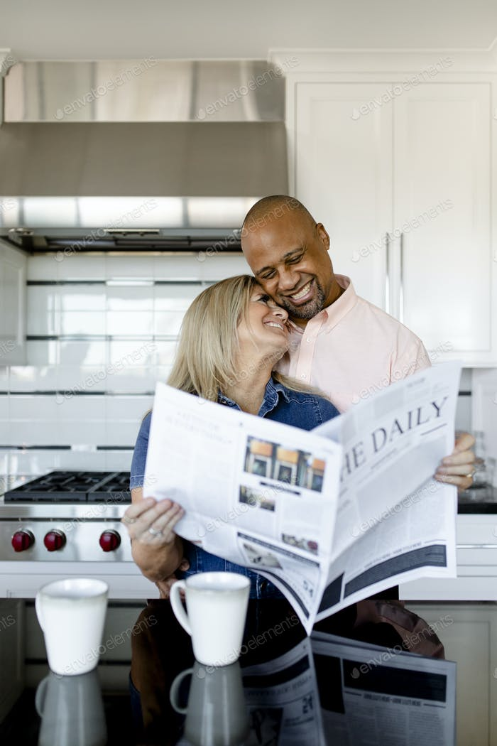 Happy couple reading the newspaper together in the kitchen