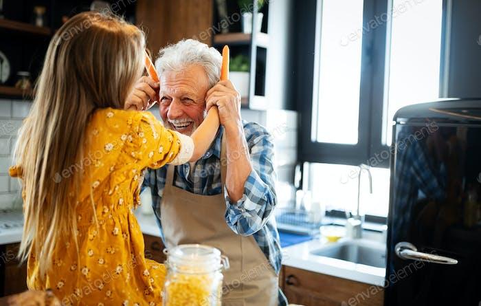 Glückliches junges Mädchen und ihr Großvater kochen zusammen in Küche