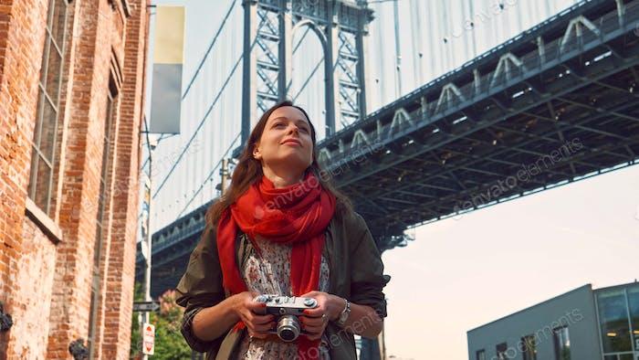 Chica sonriente en el puente de Brooklyn en Nueva York