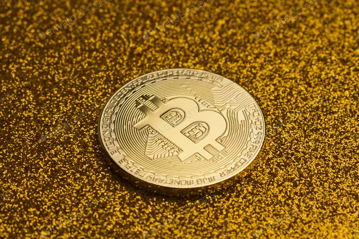 single bitcoin coin on golden glittering background