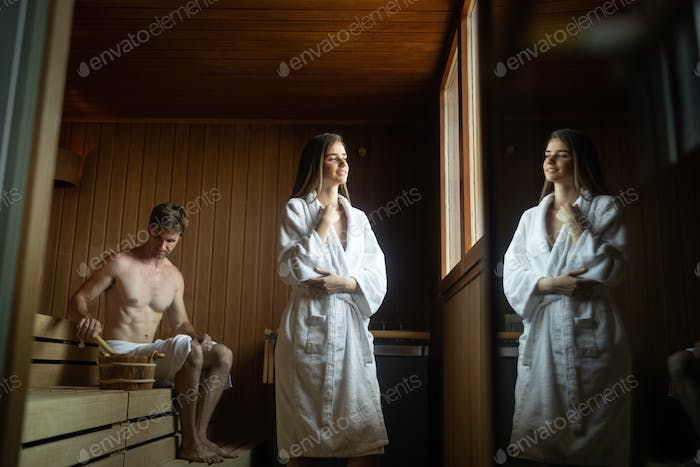 Couple relaxing in sauna and caring about health and skin