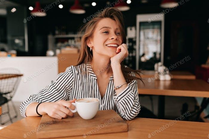Hermosa mujer joven feliz bebiendo café en una cafetería