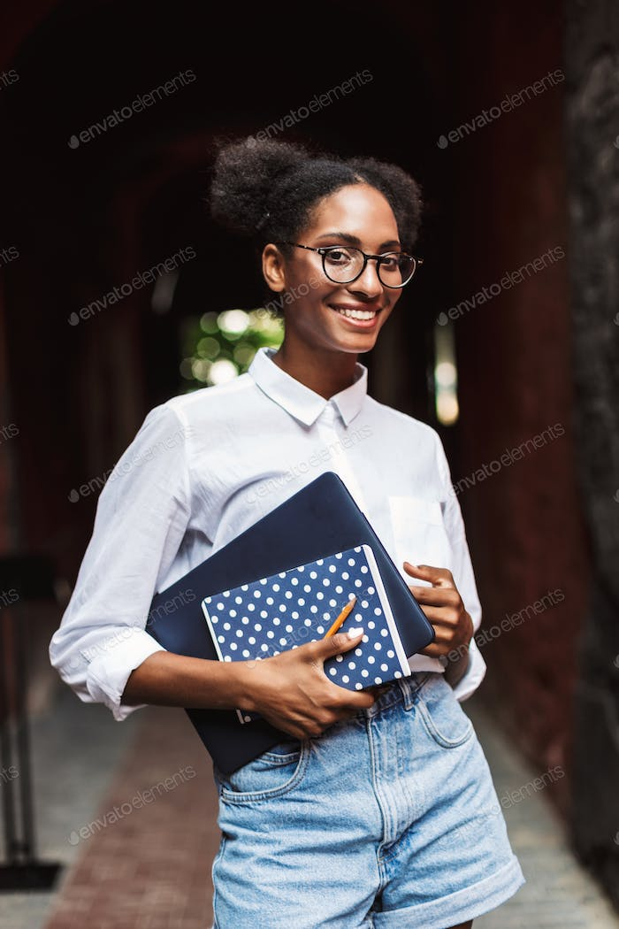 Beautiful smiling african girl in eyeglasses and shirt holding l