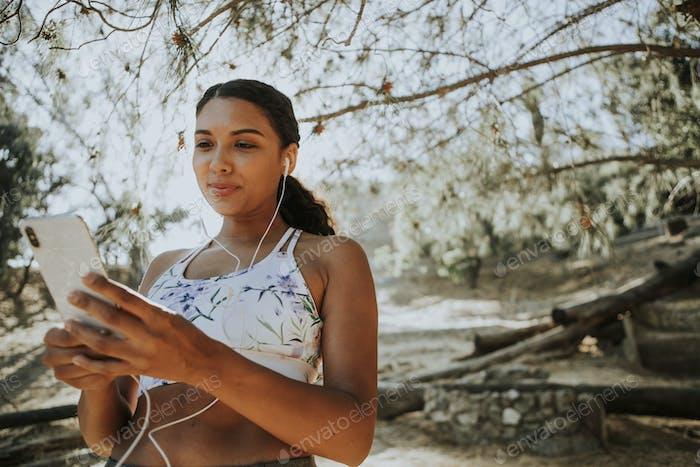 Active woman listening to music through earphones