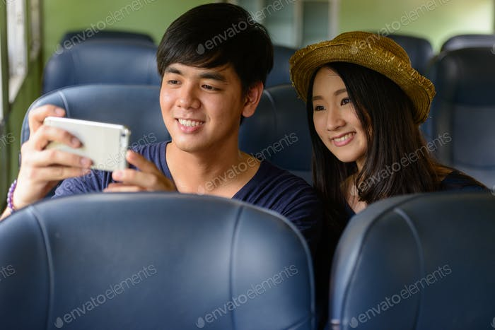 Young Asian tourist couple travelling together at the railway station