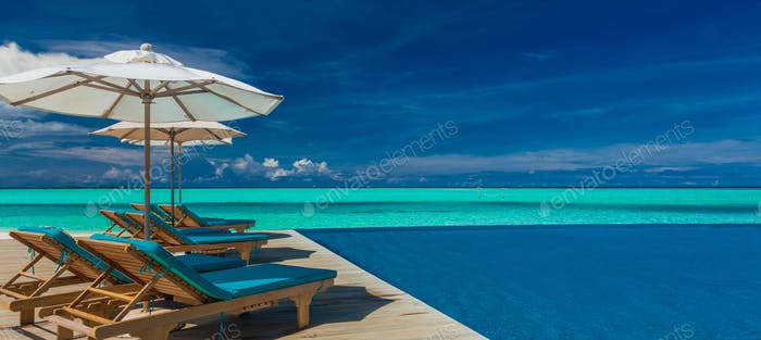 Deck chairs with umbrellas at Maldives resort with infinity pool