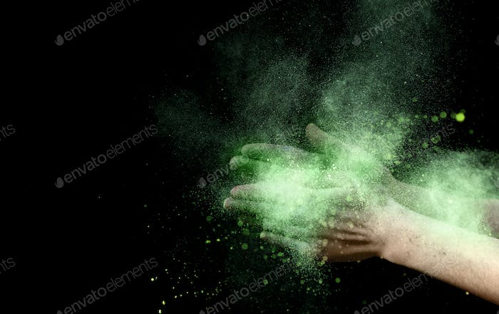 Yellow explosion of holi color powder inside clapping hands