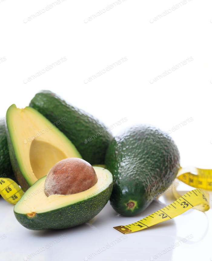 Healthy lifestyle concept. Avocados whole and half and measure tape on white background.