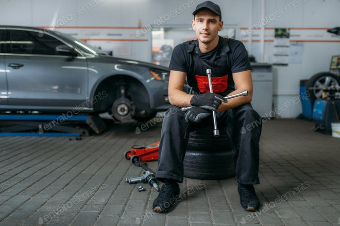 Auto mechanic sitting on wheels, tire service