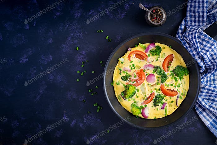 Omelette with broccoli,  tomatoes and red onions in iron skillet.
