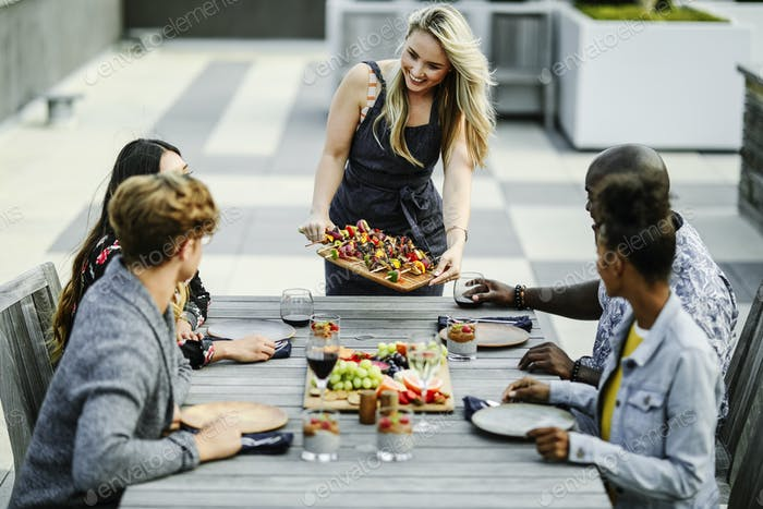 Woman serving vegan barbecue to her friends
