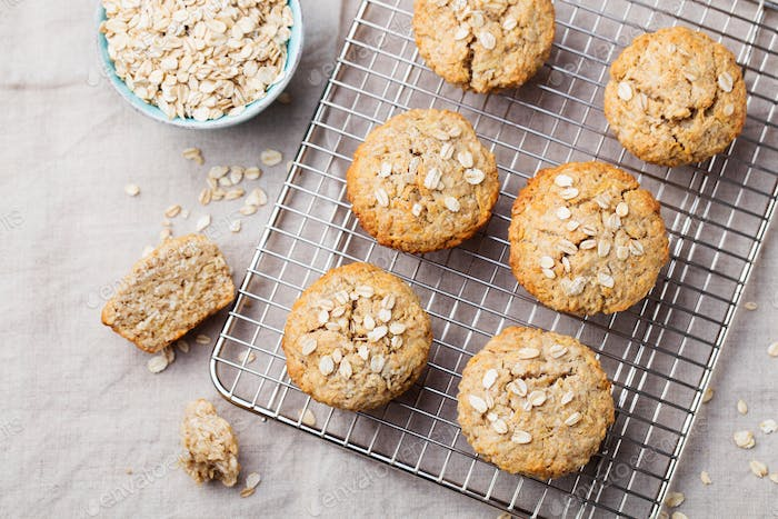 Healthy vegan oat muffins, apple and banana cakes on a cooling rack Top view Copy space