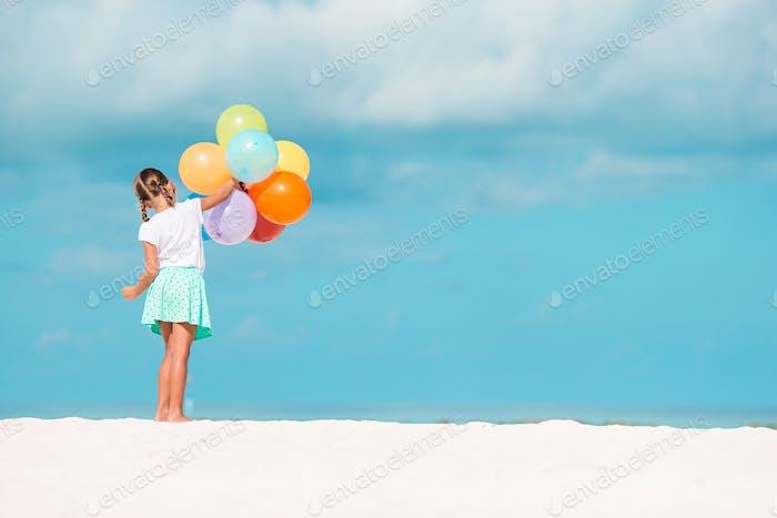 entzückend kleines Mädchen spielen mit Ballons am Strand