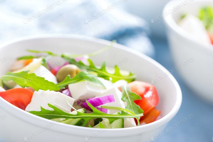 Fresh vegetable salad with feta cheese and olives in white bowl. Greek cuisine