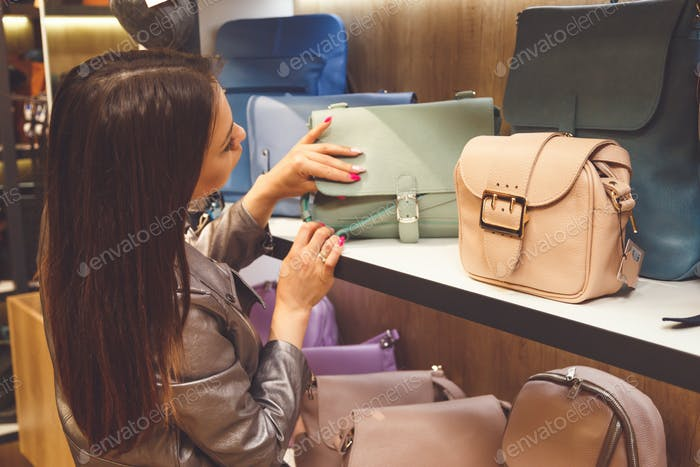 Female customer purchasing new handbag in shop