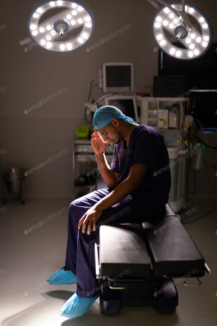 Male surgeon sitting with his head in his hand in operation room at hospital