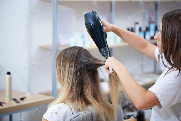 Ver drom lado del peluquero usando secador de pelo mientras peina el cabello en el salón
