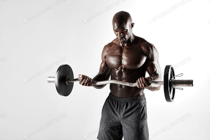 Young bodybuilder training over grey background