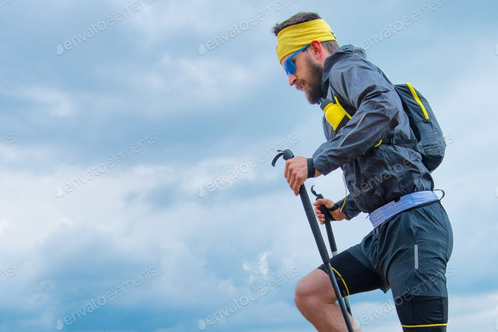 Man practicing trail running in the mountains with the sky backg