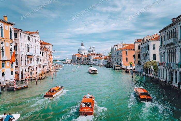 Venice, Italy. Tourist boats in Grand Canal with Basilica Santa Maria della Salute view in