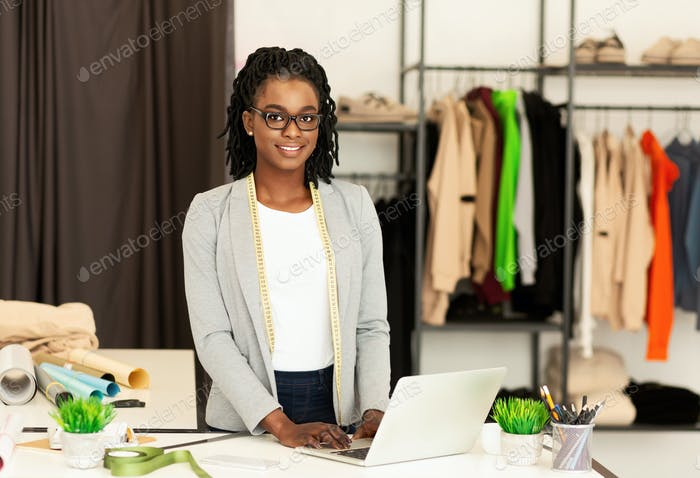 Young Couturier Girl Working On Laptop In Clothing Atelier
