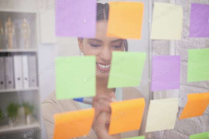 Smiling businesswoman writing on sticky notes on window in the office