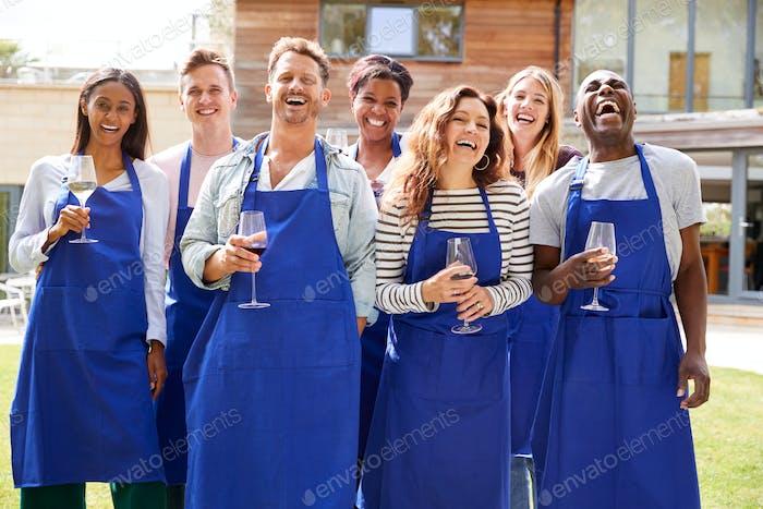 Gruppenporträt von männern und frauen besuchen cookery class entspannt im freien mit glas wein