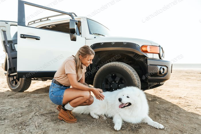 Woman cuddle a dog samoyed outdoors at the beach.
