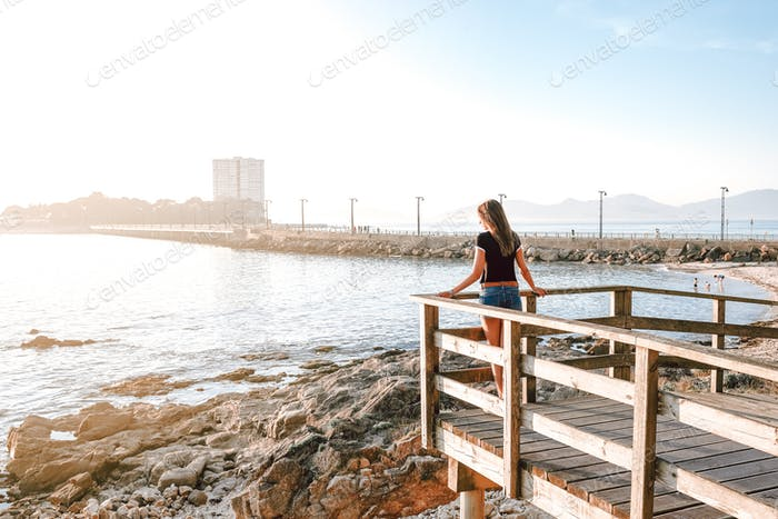 Young woman contemplating the sea from a wood structure in Vigo, in Spain