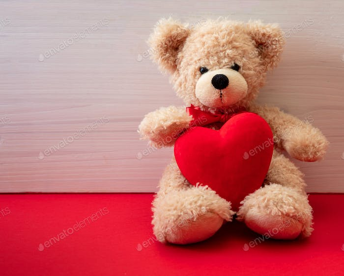 Teddy bear holding a red heart sitting on red floor. Valentines day.