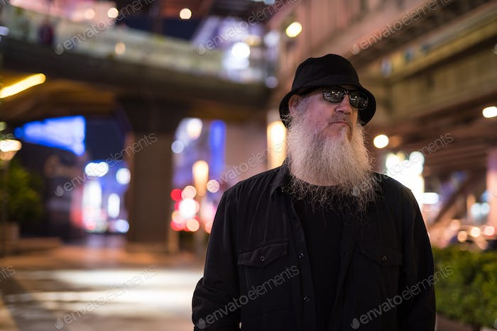 Mature bearded tourist man thinking while exploring the city streets