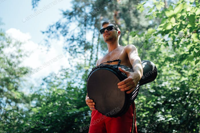 guy in glasses and red shorts playing a djembe in the woods