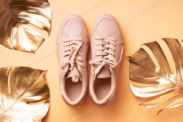 Woman fashion pink shoes and golden tropical monstera leaf on pink background with copy space. Top