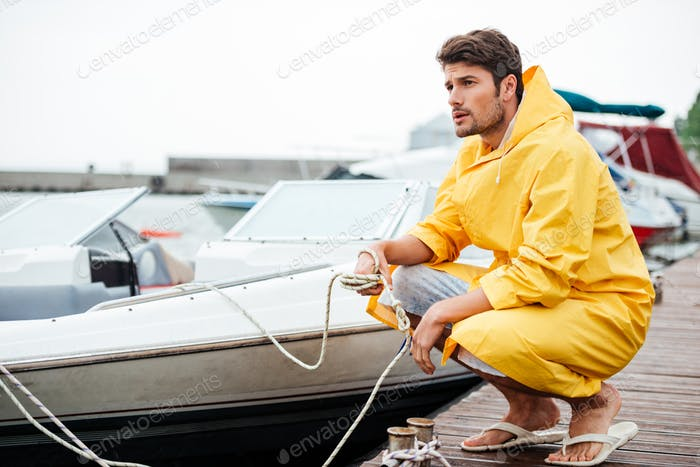Sailor in yellow cloak holding rope at the pier