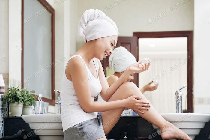 Ethnic woman moisturizing skin with lotion