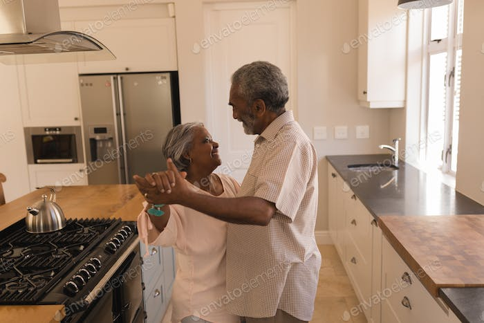 Side view of an active African American senior couple dancing in the kitchen at home