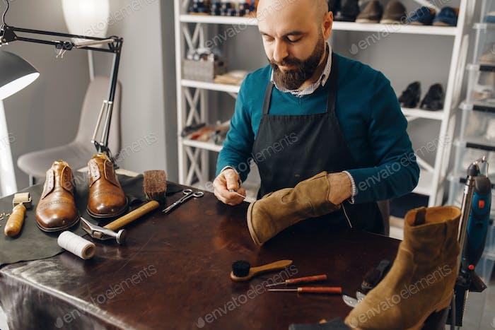 Schuhmacher näht den Schuh, Schuhreparatur