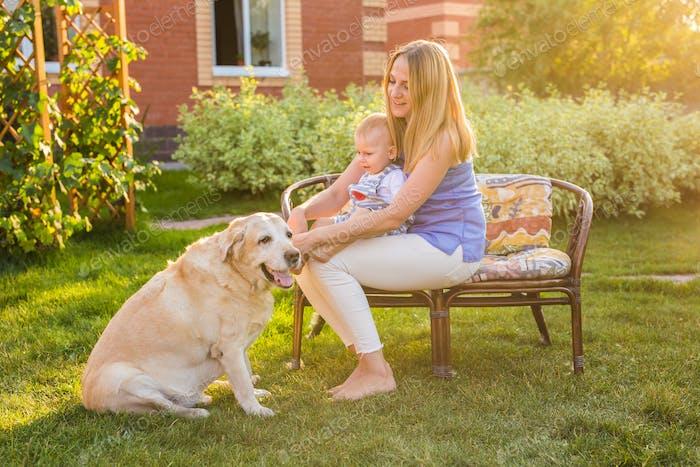 Glückliche Familie spielt mit ihrem Hund an einem sonnigen Tag.